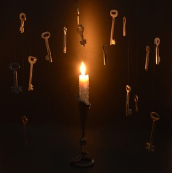 Single burning candle in candlestick with hanging metal keys