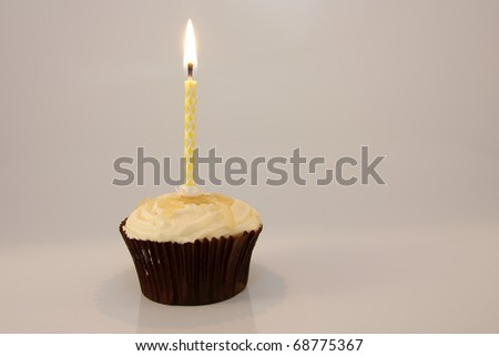 Single candle in lemon cupcake against a white background