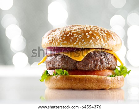 single cheeseburger with silver background and selective focus