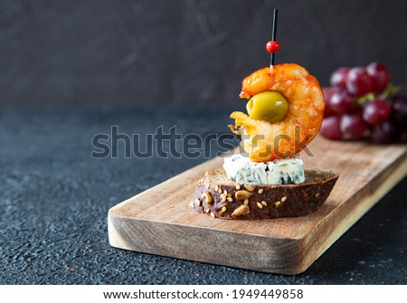 Single classic Spanish tapas lie on a wooden board. The tapas consist of shrimp, gorgonzola, green olive and bruschetta skewered for canapes - close-up Foto stock ©