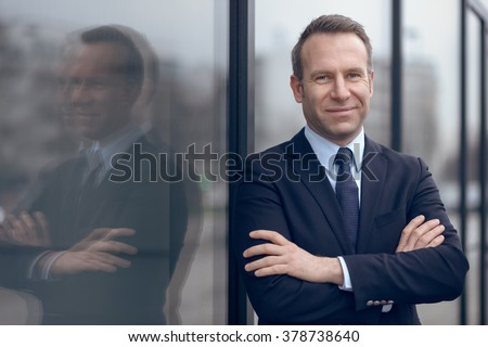 Single confident and handsome male businessman in blue suit and necktie with grin leaning on window outdoors