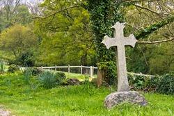 Single cross headstone in graveyard