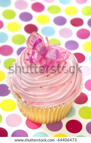 Single cupcake with pink frosting and a butterfly, on polka-dot background.