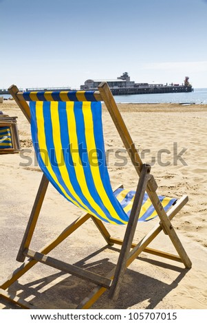 Single deck chair on the beach at Bournemouth, Dorset,UK with pier in the background