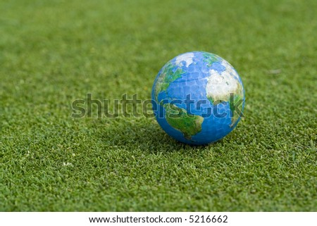 Single earth golf ball lying on green grass