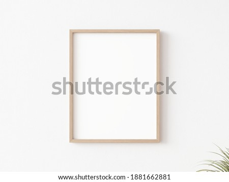 Single empty vertically oriented rectangular picture frame with thin wooden border hanging on white wall. 3D illustration.