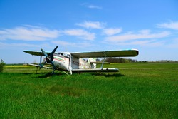 Single-engine biplane agricultural aircraft landed on a green field under blue sky.