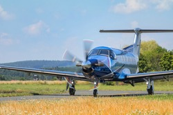 Single-engine turboprop blue airplane. Blue Airplane on runway. Front View.