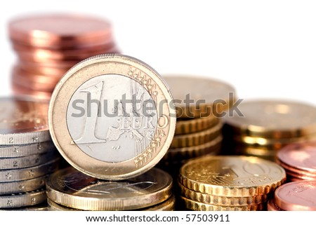 Single Euro coin balanced on stacks of varying denominations of Euro coins.  White background