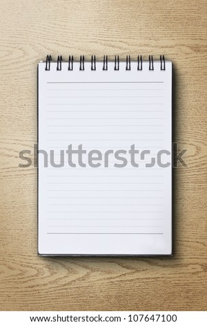 single face notebook on wood background
