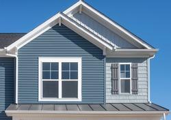 Single family home with natural wood look rough shake finish vinyl Bermuda blue shake and shingle pacific blue horizontal siding, dark metal roof, double pane window with dark shutters, snow trim,