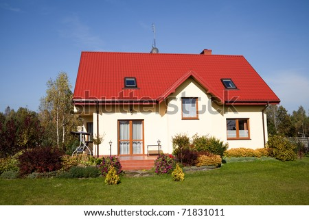 Single family house in bright yellow color against blue sky
