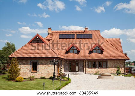 Single family house of brick with red roof over blue sky