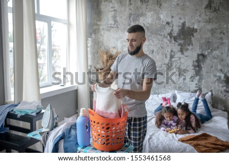 Single father. Single father preparing kids clothing for laundry while daughters playing video game