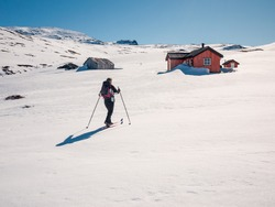 Single female backcountry skiier approaching a small cottage in the Norwegian Mountains at easter at a sunny day