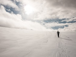 Single female cross-country skiier climbing uphill in a partly groomed track towards the sun breaking through clouds in the Norwegian Mountains at easter