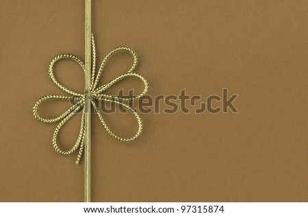 Single festive gold ribbon bow on plain brown background with room for your text