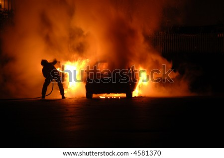 Single fire fighter struggles alone to put out blazing car fire, moving trying to dodge the heat and at the same time aim the hose