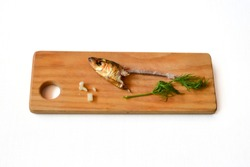 Single fish head with bone and the green additives on the wooden board, white background. A poor diet sample for humans.