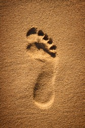 Single foorprint in yellow brown sand on the beach as a symbol for recreation or vacations