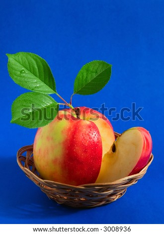 Single fresh red delicious apple with drops of water in a basket
