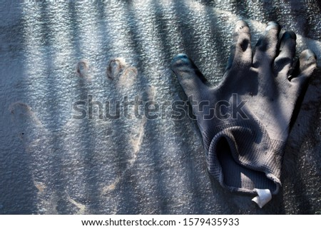 Single garden glove and a handprint on a tempered glass table. Conceptual, mysterious photography.