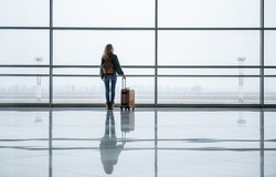 Single girl realizing an old dream. She is traveling with bag to foreign country. Copy space in right side