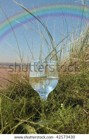single glass of pure natural water standing on the beach dunes in kerry ireland in the rain with a rainbow in the background.