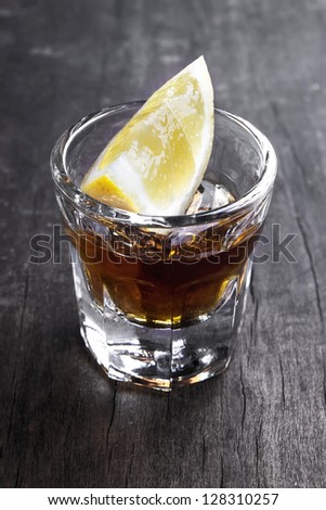 Single glass of tequila with lemon on table