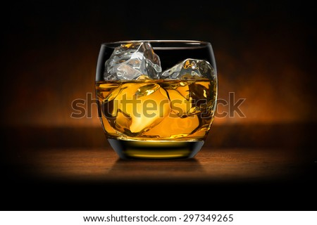Single glass of whisky whiskey bourbon on ice on top of a wood bar table and wooden background