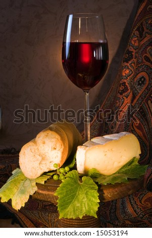 Single glass with red wine, cheese and bread - stock photo