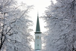 Single green and white color minaret of a small mosque in winter. Trees with rime and snow around