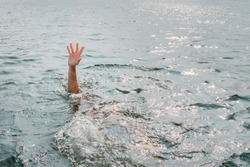 Single hand of drowning man in water asking for help