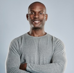 Single handsome black man with folded arms, confident expression and pleasant smile in gray compression shirt over neutral background