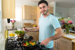 Single handsome man cooks at home alone a nutritious meal lunch dinner chef