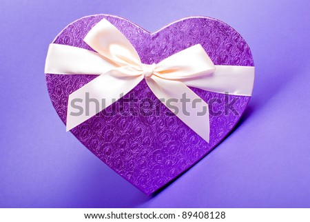 Single heart gift box with ribbon on blue background.