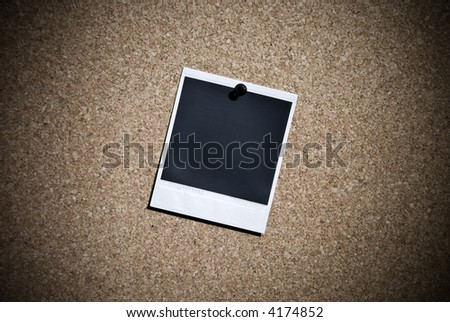 single  instant photo hanging on a message board