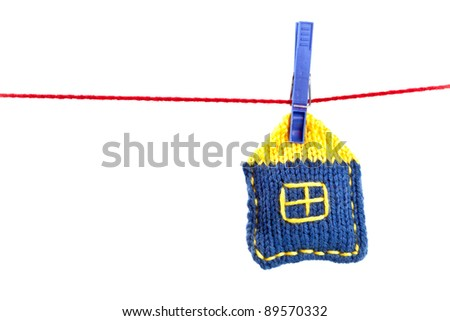 single knitted house on a red string isolated on white background - stock photo