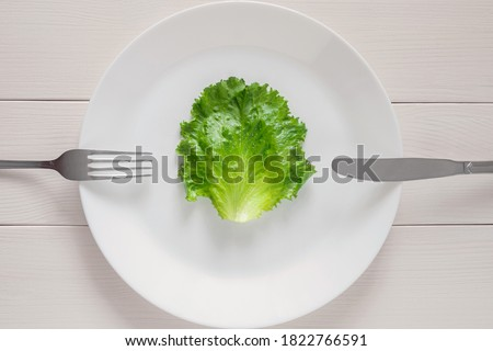 single lettuce leaf on the plate with fork and knife, detox mono diet for weight loss Stock photo ©