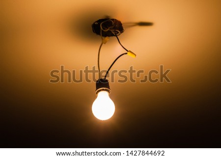 Single light bulb hanging on exposed wires from ceiling illuminating dark area. #1427844692