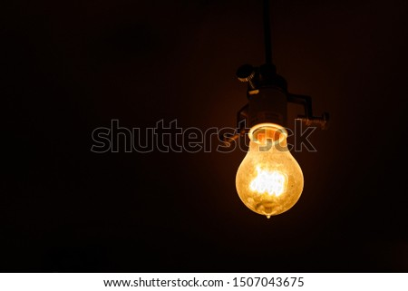 Single lightbulb hanging from a wire in a dark room with a warm glow #1507043675