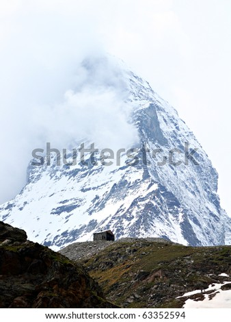 single, lonely small house in front of the vertical rock masses of mountain Matterhorn in Switzerland - stock photo