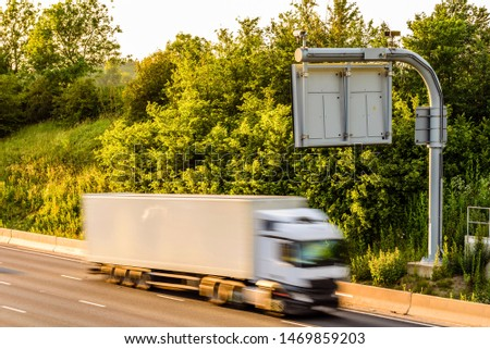 single lorry truck on uk motorway road under information display at sunset #1469859203