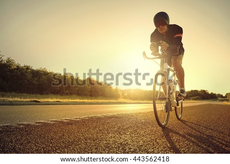 Single male bicyclist back lit by bright yellow sunlight while racing his bike on road bike at sunrise #443562418