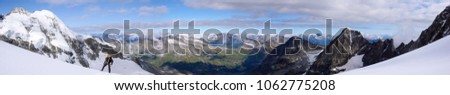 single male mountain climber on a high glacier in the Swiss Alps with a great view #1062775208
