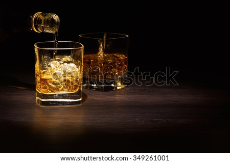 Single Malt Whiskey in a glass on a wooden table top.
