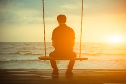 Single man alone while swinging on the beach at sunset
