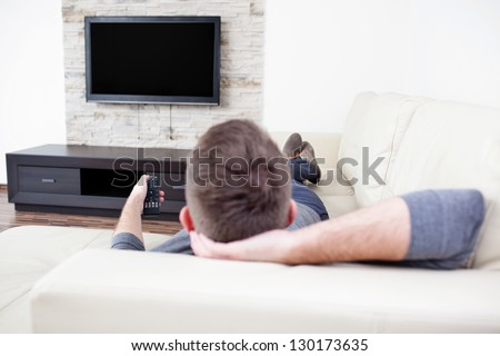 Single man on the couch watching tv, changing channels