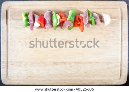 Single meat stick on wooden bread board with space for text of design - stock photo