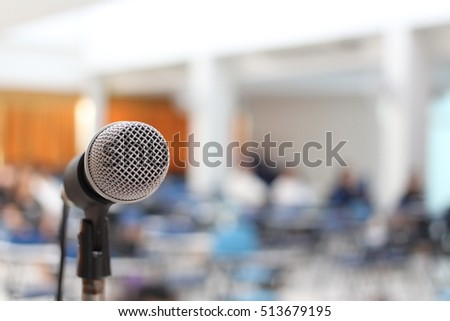 single microphone on stage with blur conference room background